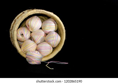 A colorful basketful of yarn lays on it's side.