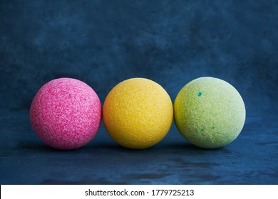 Colorful bath bombs on blue background. Copy space for text.