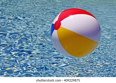 Colorful Beach Ball Floating In Blue Swimming Pool
