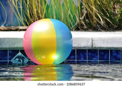 A colorful beach ball floating in a swimming pool.