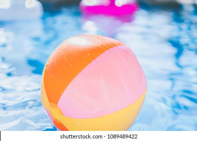 colorful Beach ball floating in swimming pool. Abstract concept of summer vacations, relaxation and have fun in the sunshine day