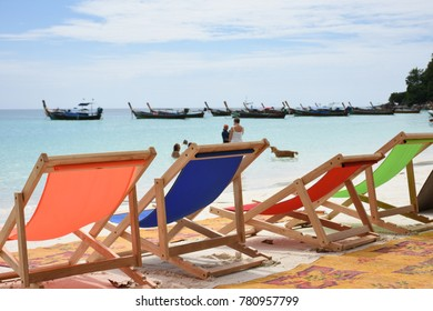 Colorful beach chairs in the sand facing the sea.