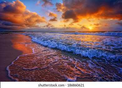 Colorful beach destination sunrise or sunset with beautiful breaking waves