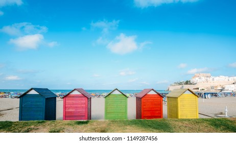 Colorful beach huts on Peniscola beach, located on Costa del Azahar in the Castellon province of Spain. This popular tourist destination is located on a rocky headland.