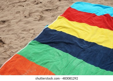 Colorful beach towel on the sand on a bright sunny day, red yellow blue green orange