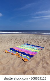 Colorful beach towel on sand with ocean and sky background. Vertical.