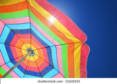Colorful beach umbrella against sunny blue sky