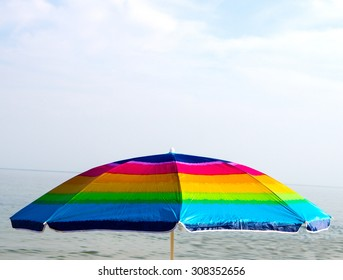 Colorful beach umbrella on sea background and blue sky