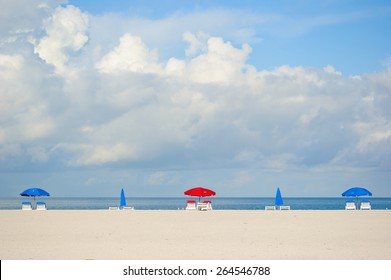 Colorful beach umbrellas on tropical Clearwater Beach with uncluttered sand and sky area for text.