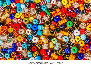 Colorful beads on a wooden surface. Variety of shapes and colors to make a bead necklace or a string of beads to please a woman of fashion.