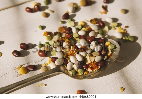 colorful beans with silver spoon on white wood
