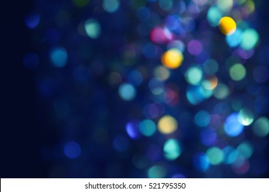 Colorful beautiful blurred bokeh background with copy space. Holiday texture. Glitter multicolored light spots on navy blue backdrop, defocused