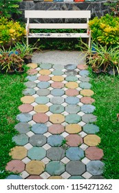 Colorful and beautiful cement blocks in walkway with white chair in garden