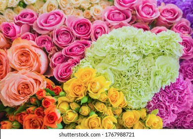 Colorful beautiful flowers wall background - roses and carnations at studio, flower shop - close up view. Floristry, romantic, holiday, birthday, valentine day, wedding, celebration concept