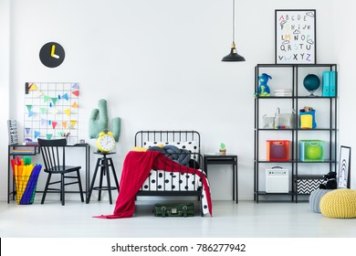 Colorful bedroom for a child with red blanket on metal bed frame and black desk next to a basket with tissue paper