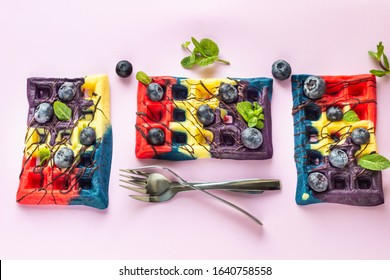 Colorful Belgian waffles decorated with chocolate glaze, fresh blueberries and mint. Pink paper background.