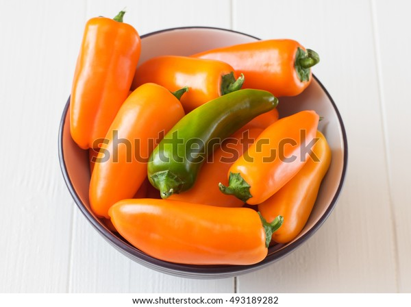 Colorful bell peppers in a bowl on a wooden table. Healthy food concept.