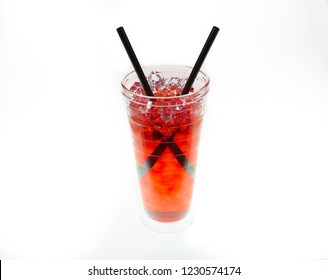 Colorful beverage with two black straws and with ice/condensation isolated against white background.