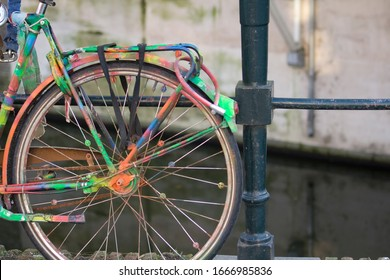 Colorful bicycle locked on a Dutch canal