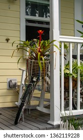 Colorful bicycle with madi gra style beads sitting on a relaxing front porch of an island style house with tropical plants