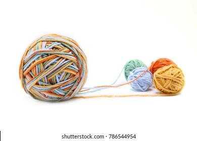 Farbige, große Fadenkugel aus vier Farbfäden. Baumwollgarnbälle einzeln auf weißem Hintergrund. Verschiedene Farben (orange, gelb, grün, blau).
