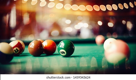 Colorful billiard balls on a green billiard table. Gambling game of Billiards. Billiard ball with number nine.