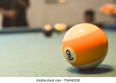 Colorful billiard balls on a pool table,soft focus,numbers nine