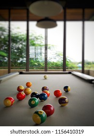 Colorful Billiard balls in Pool Table with gray felt at bar and living room on roof top of hotel