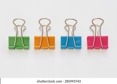 Colorful binder clips on white background