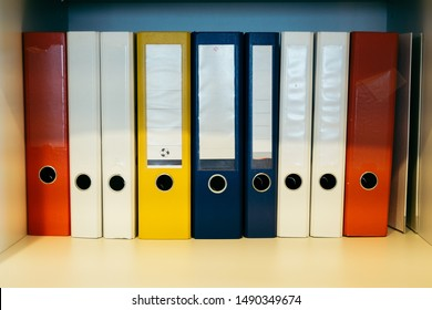 Colorful binders on a shelf with empty labels