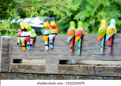 Colorful of bird statues on the brown brick wall,waterfall model with green fresh nature background.Beautiful object for park decoration.Selective focus.