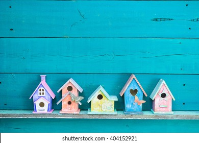 Colorful birdhouses with butterfly on shelf by antique rustic teal blue wood background; pink, purple, yellow, orange birdhouses with wooden copy space