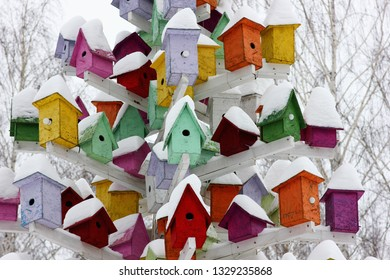 colorful birdhouses on a tree in the winter park