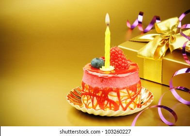 Colorful birthday cake with candle on golden background