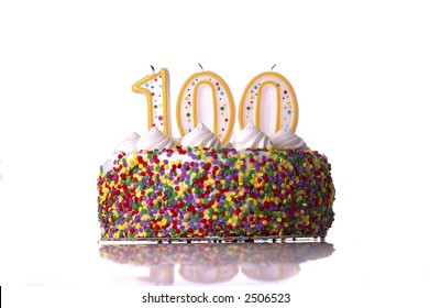 A colorful birthday cake with candles shaped like the number 100. White background.