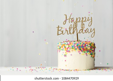 Colorful Birthday Cake With Golden Happy Banner And Falling Sprinkles