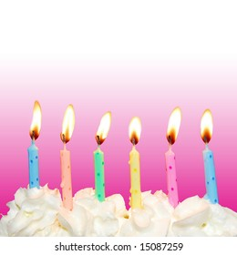 Colorful birthday candles on cake with whipped cream and pink square background