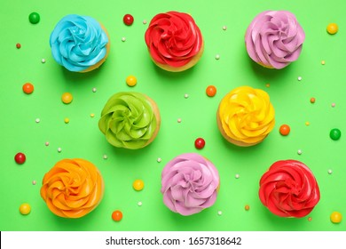Colorful birthday cupcakes on green background, flat lay