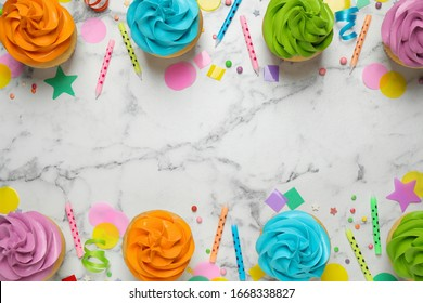 Colorful birthday cupcakes on marble table, flat lay. Space for text