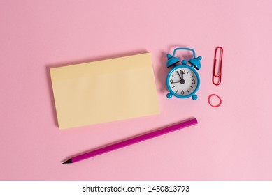 Colorful blank notepad message rubber band marker pen small alarm clock wakeup clip colored background empty text important events home office school house everywhere