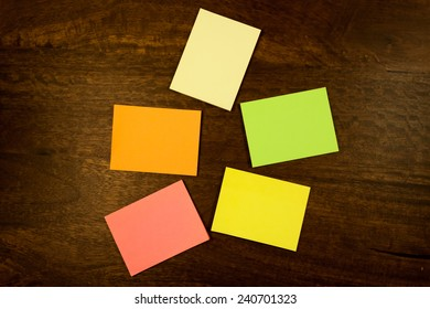 Colorful blank sticky notes lying on a  dark mahogany table. View from the top.