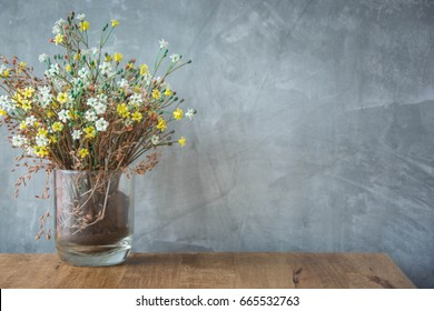 colorful blossoms in a transparent vase on a wooden table with gray wall space background