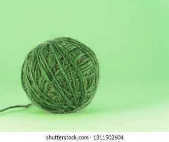 Colorful blue and green yarn ball on green background, isolated, texture.