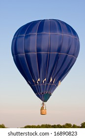 A colorful blue hot air balloon at a festival is suspended in mid-air on a clear day.