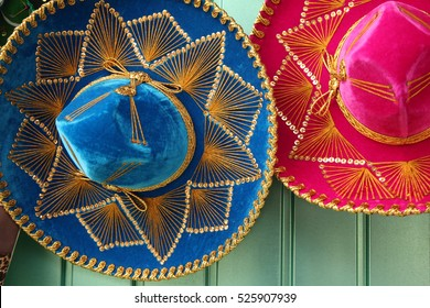Colorful blue & pink Mexican hats hanging on a green door, Mexico.