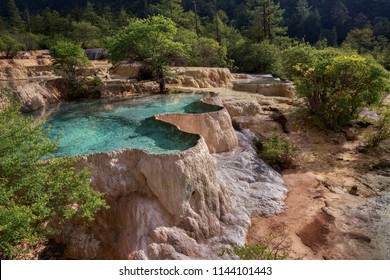 Colorful blue pools of water in Huanglong Scenic Area in Sichuan Province, China. Beautiful and exotic natural geological landforms caused by erosion over time, yellow dragon natural terraces