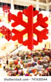 Colorful blurred background of Christmas decoration over a crowded shopping center