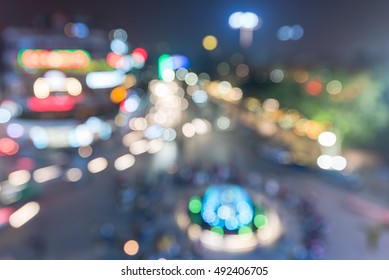 Colorful blurred image light trails of running vehicles on busy intersection locate next to Hoan Kiem (Sword lake) in old quarter Hanoi capital, Vietnam night. Aerial view motion cityscape,bokeh light
