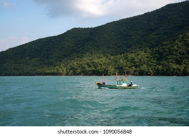 Colorful boat, floating calmly in the emerald green ocean with the mountain in the back