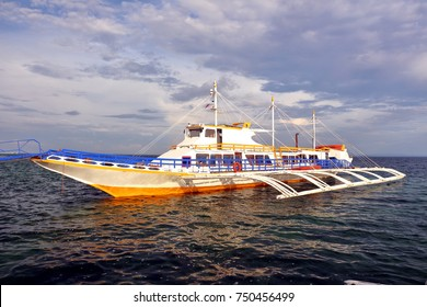 A colorful boat floating the dark seawater in the port of Cordova island in Cebu.